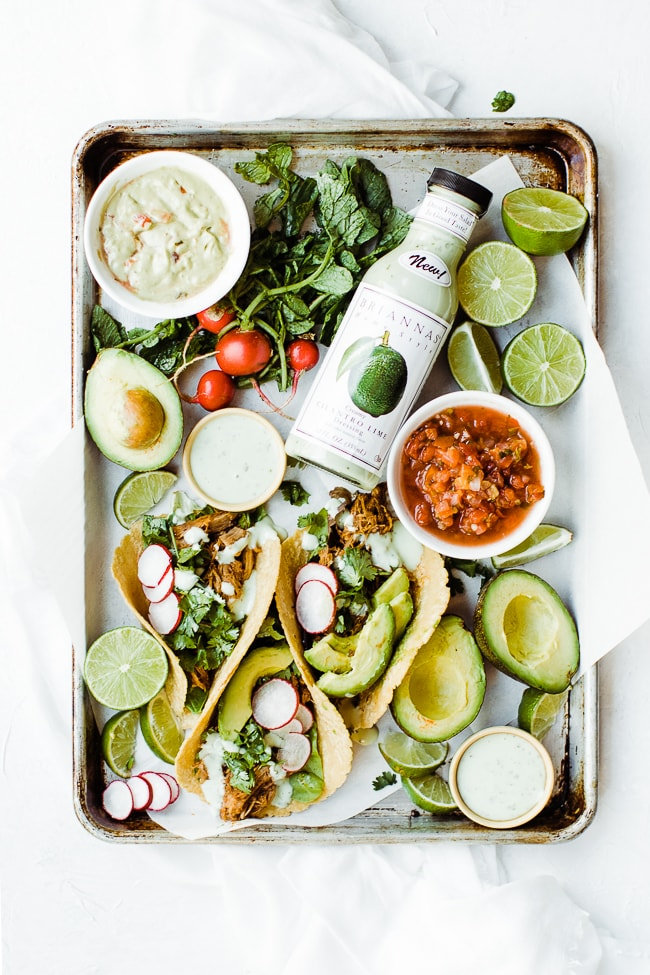 tacos and condiments on platter with cilantro lime dressing