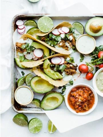 three sweet pork tacos with sauce, salsa and avocado
