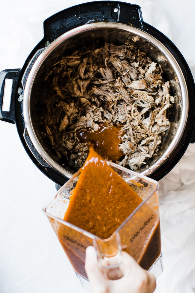 sauce being poured into shredded pork