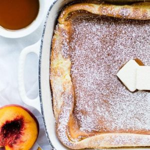 german pancakes with butter and powder sugar, syrup and peaches