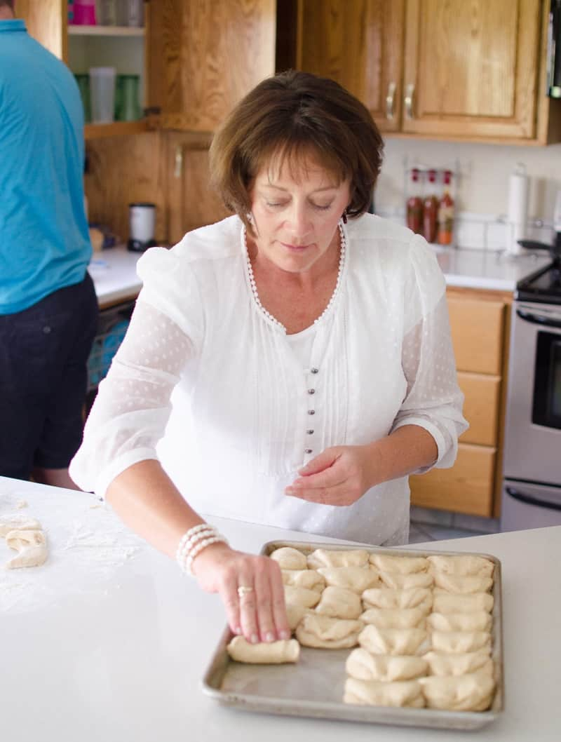 woman folding dinner rolls on pan