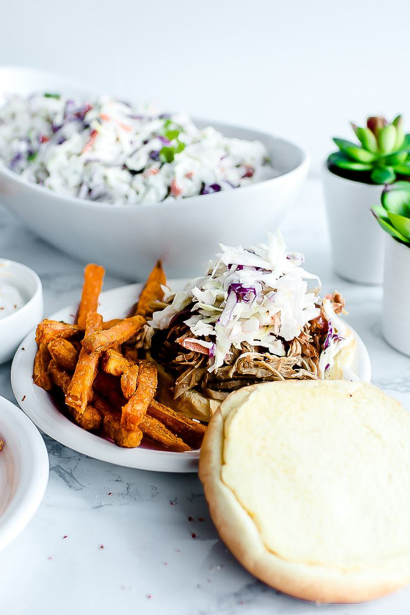 The Best Pulled Pork Recipe on burger bun, served with fries. coleslaw in the background