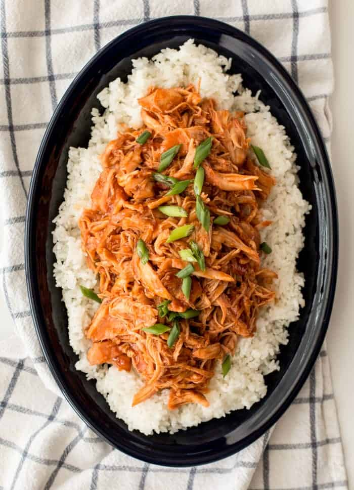 apricot chicken topped with chives, on top of rice in slow cooker