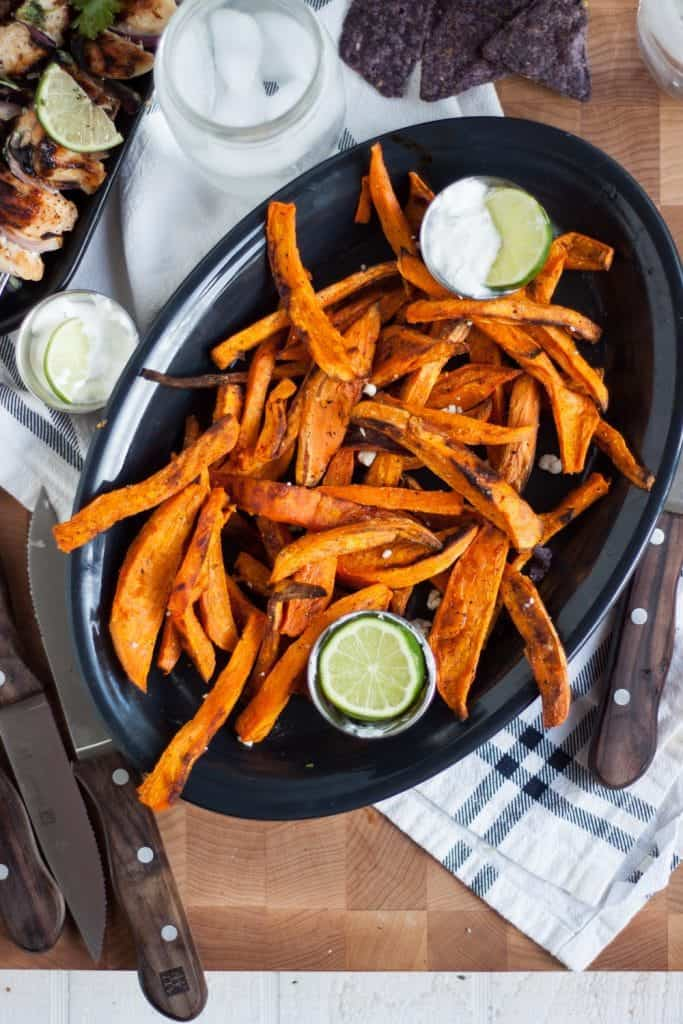 A close up of sweet potato fries on a black plate with dipping sauces