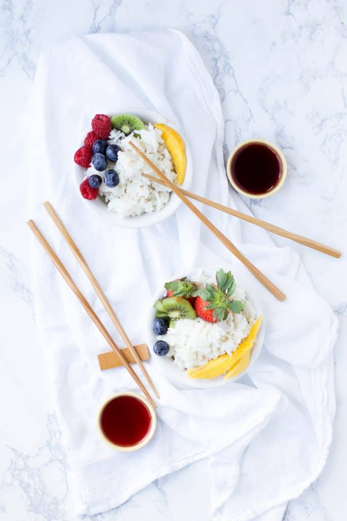 Easy Coconut Rice in two bowls with fruit and chop sticks