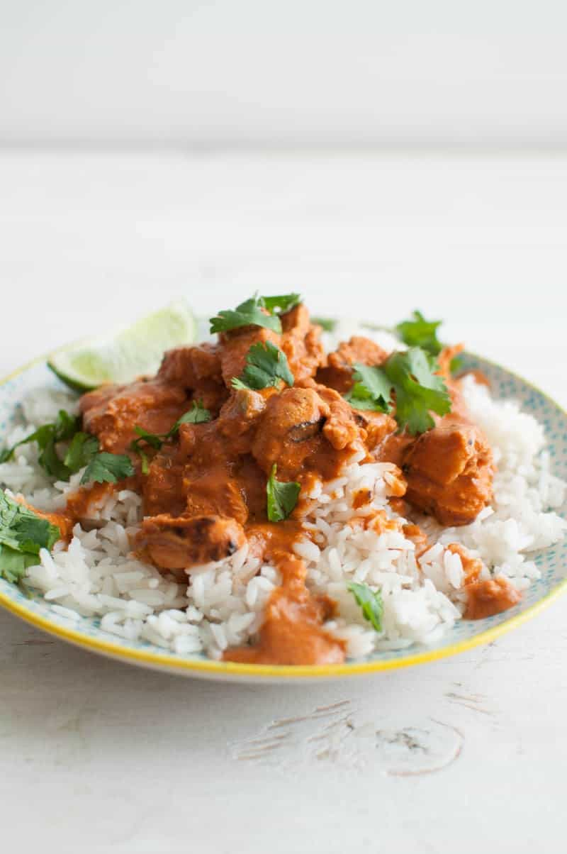 Chicken Tikka Masala on plate with green garnish and halved limes to the side