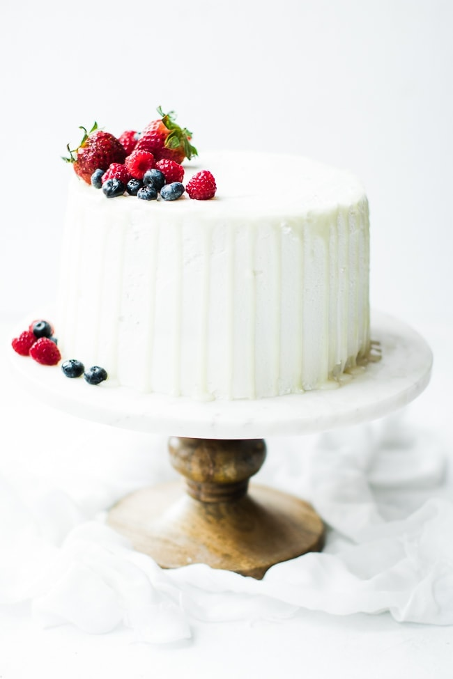 white cake with drips and fruit on top