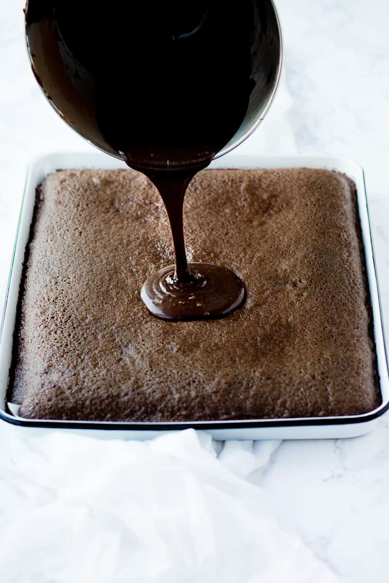 Scotch Chocolate Cake on a tray with chocolate icing pouring on top from a bowl