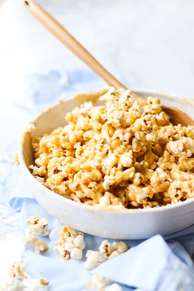 caramel popcorn in a white bowl with a wooden serving spoon