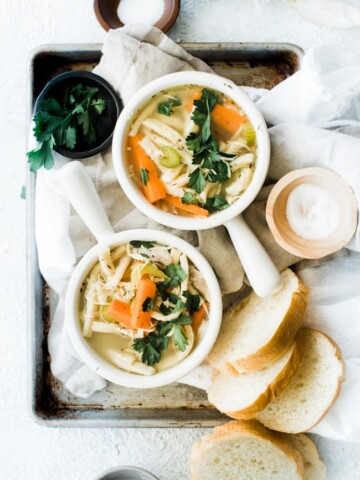 two bowls of chicken noodle soup with bread