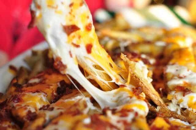 Cheesy potato fries with stretchy cheese pulling as one gets picked up