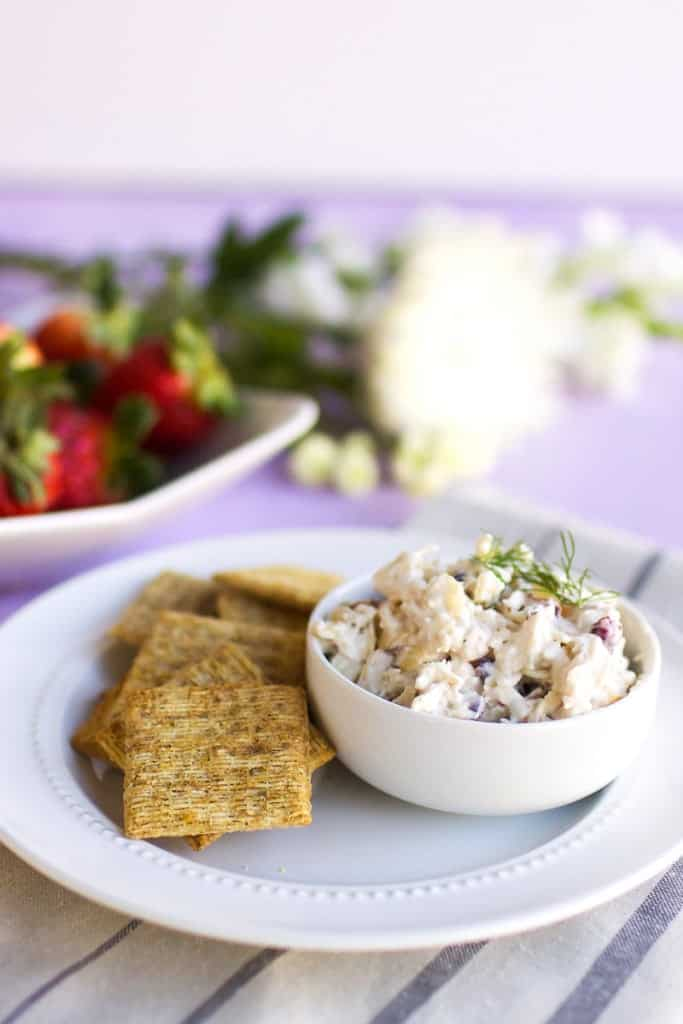 Chicken Salad in small white bowl with dill garnish, crackers on the side