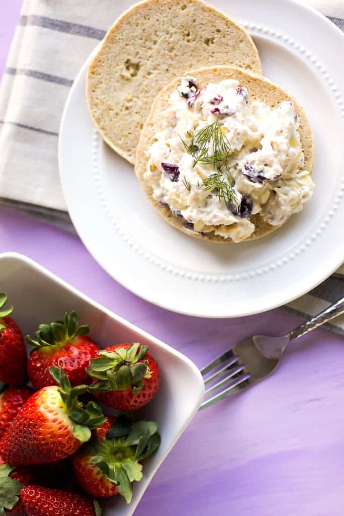 Chicken Salad on sandwich thin, overhead shot. fresh strawberries in white square bowl on the side