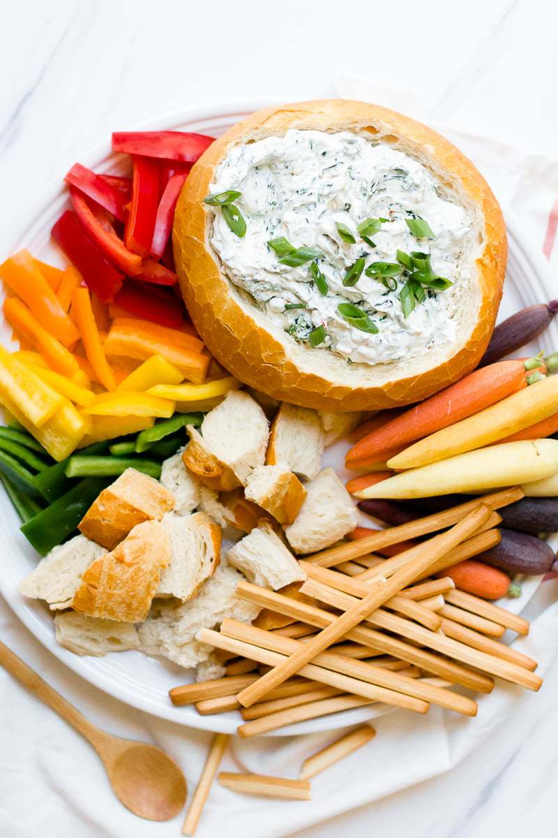An Easy Spinach Dip in a bread bowl with chopped vegetables