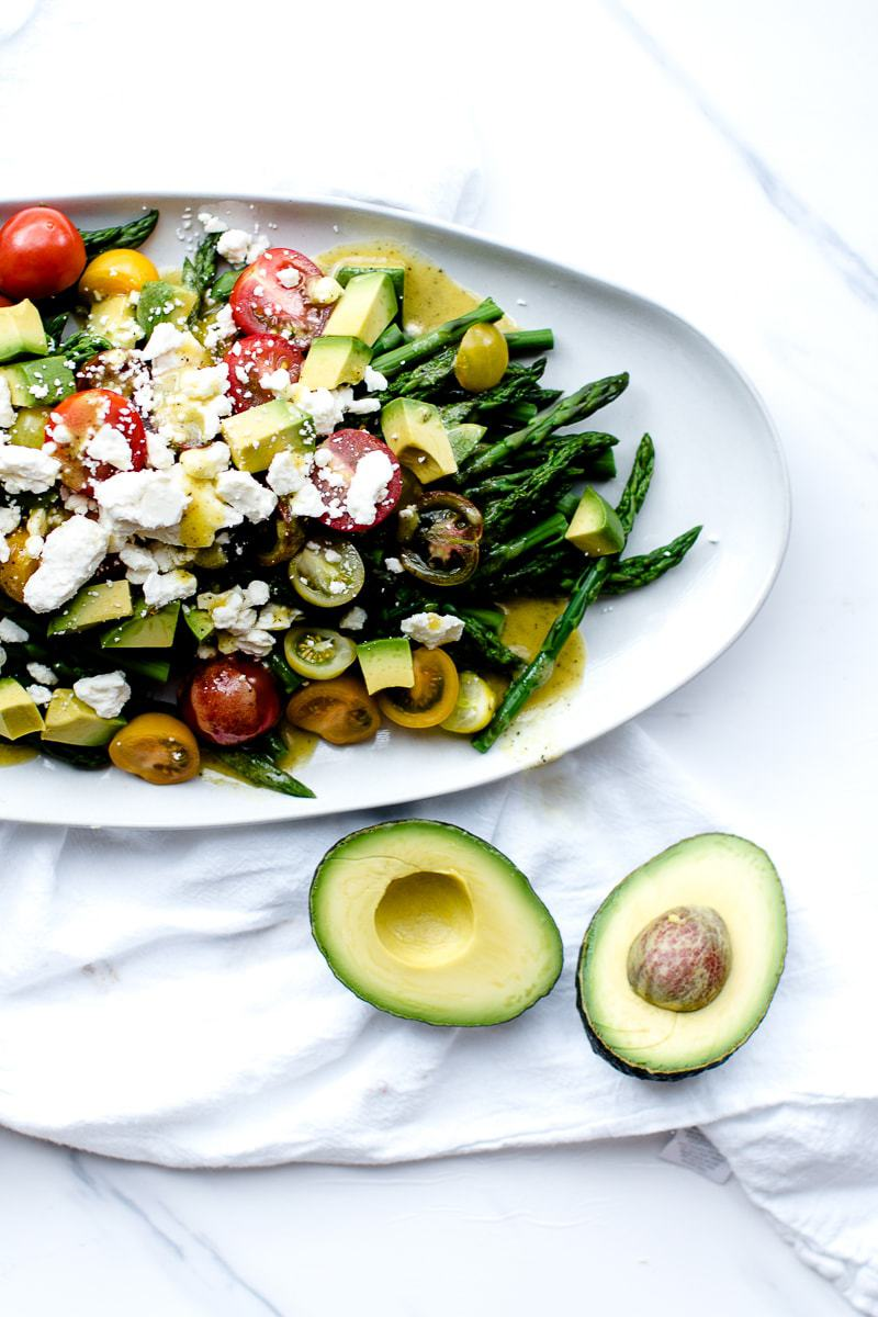 summer asparagus salad on a white serving dish with a halved avocado
