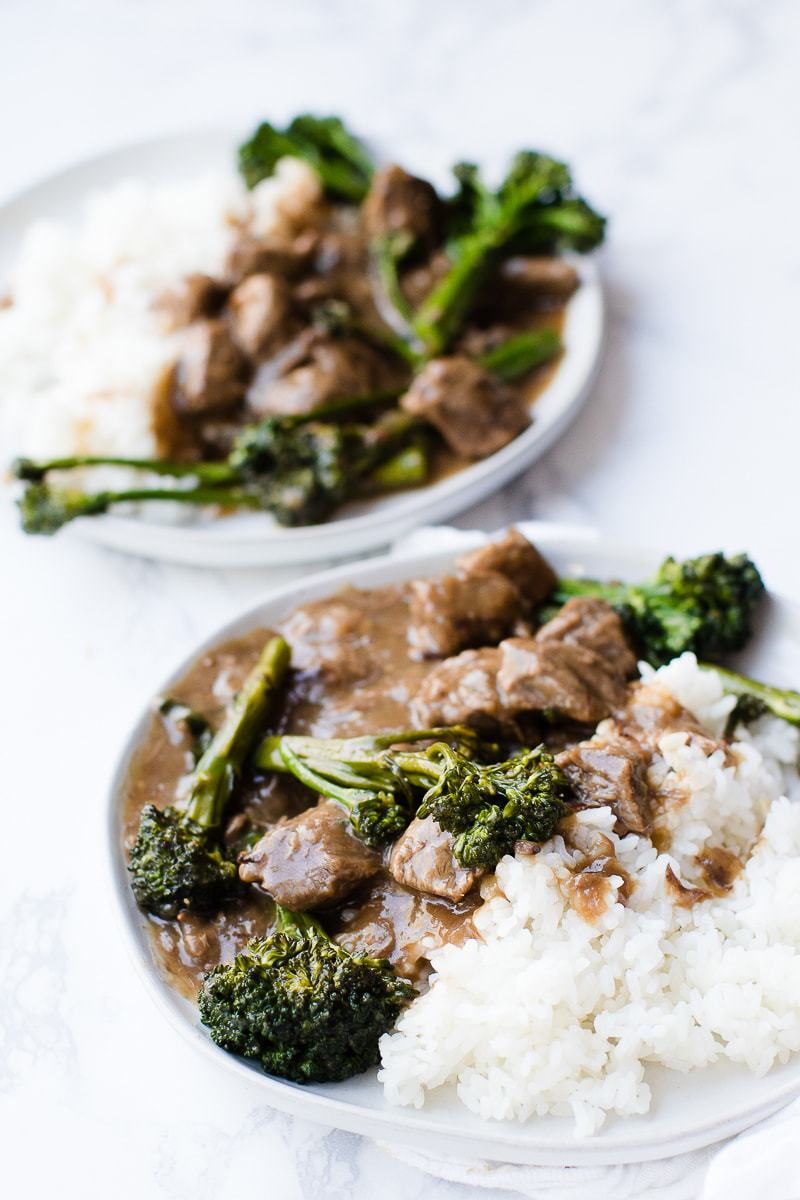beef and broccoli with rice on a white plate
