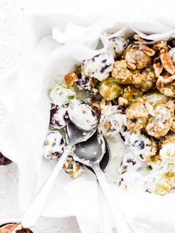 up close rectangle dish of grape salad and brown sugar topping 3 spoons dipping into the dish
