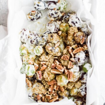 rectangle dish of grape salad and brown sugar topping 3 spoons dipping into the dish