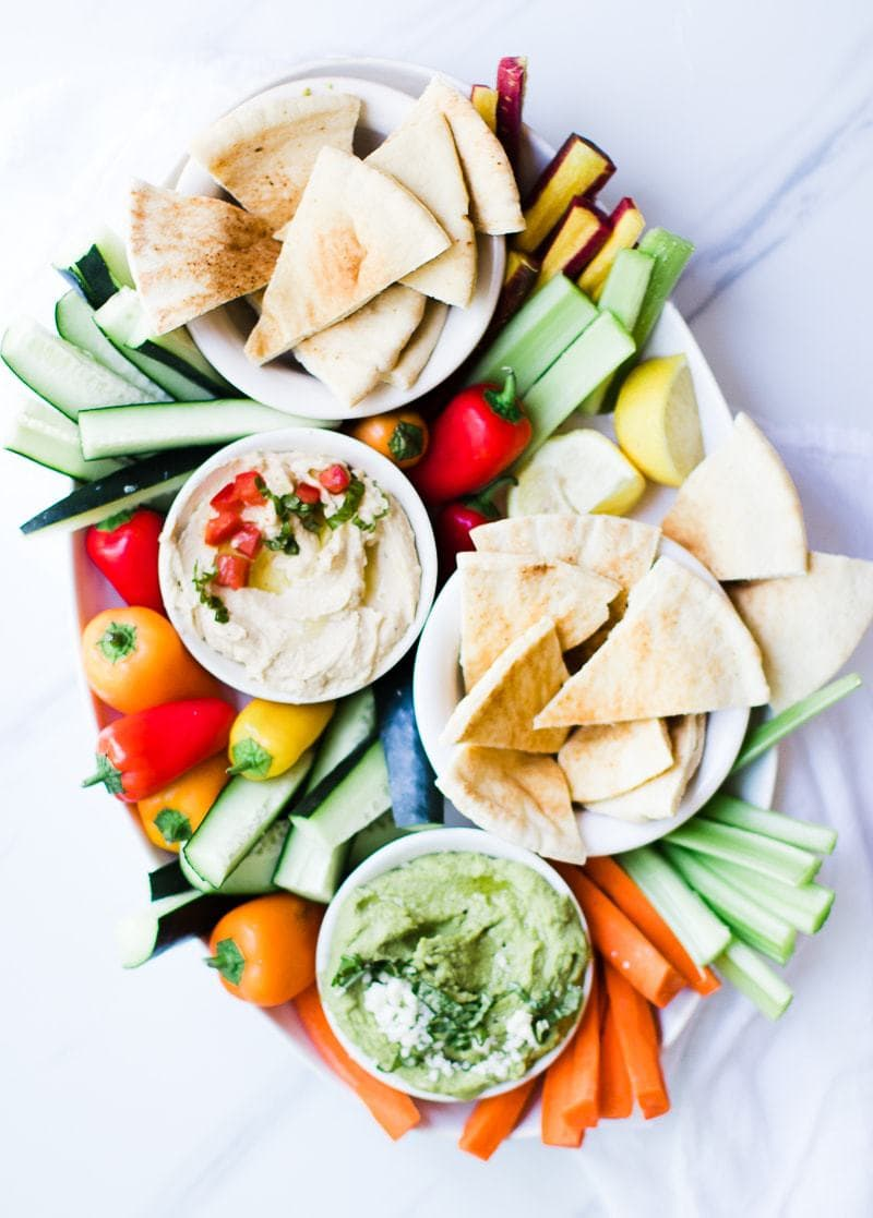 hummus, pita bread, and vegetable dippers on a large platter