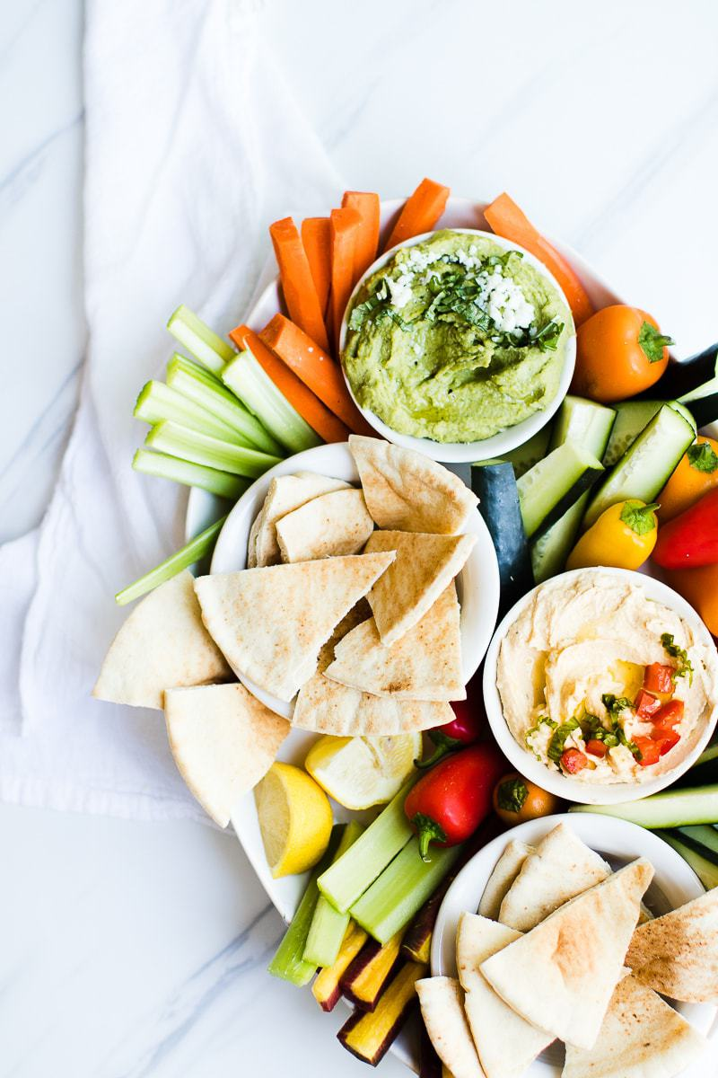 hummus, pita bread, and vegetable dippers on a serving plate
