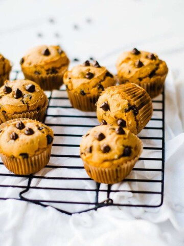 Pumpkin cake mix muffins with chocolate chips on a wire cooling rack.