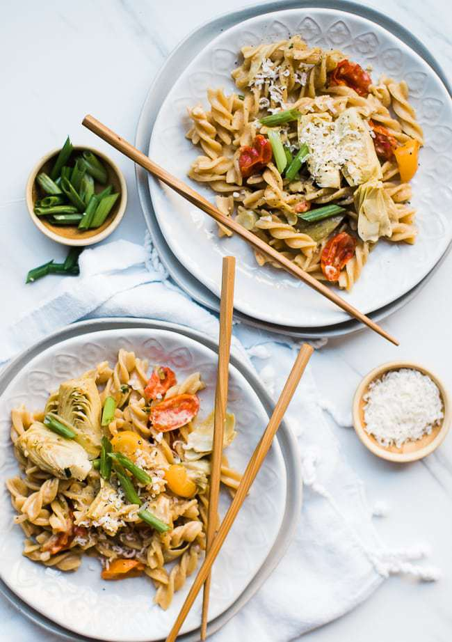 two plates of creamy artichoke pasta with chopsticks