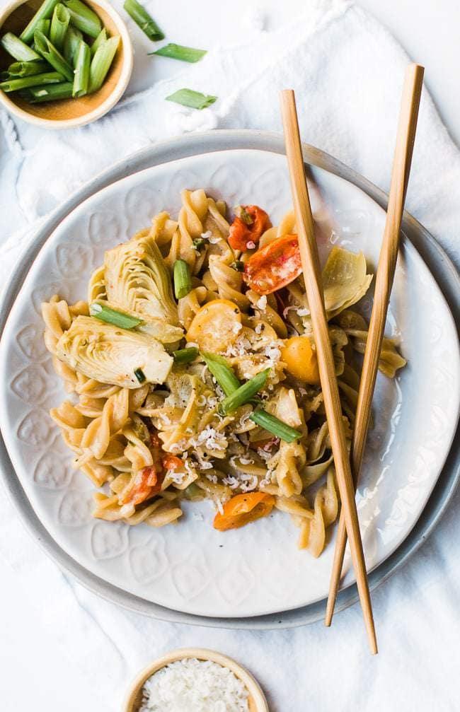 creamy artichoke pasta with chopsticks on plate