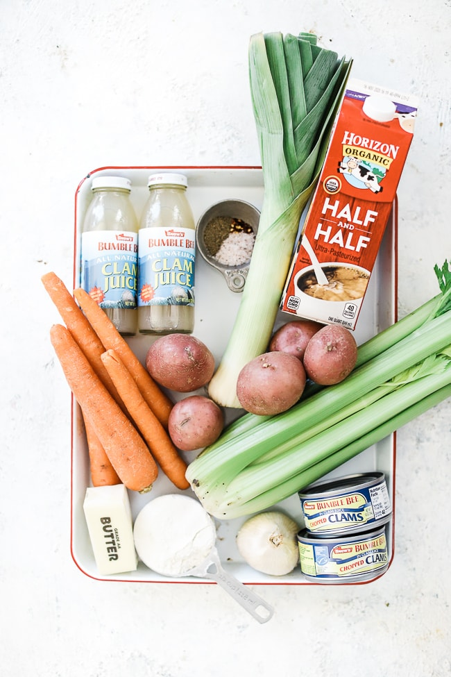 The indgredients needed for clam chowder on a baking sheet. They include clam juice, potatoes, carrots, celery, flour, butter, clams, cream, and leaks.