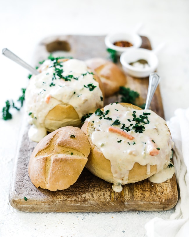 A 3/4 view shot of clam chowder is bread bowls. the chowder is garnished with fresh parsley and dripping out the bread bowls. The bread bowls are atop a wooden cutting board.