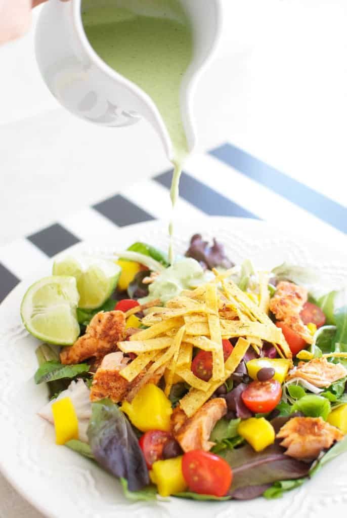 Caribbean Salad with Spicy Salmon and Creamy Tomatillo Dressing being poured on salad