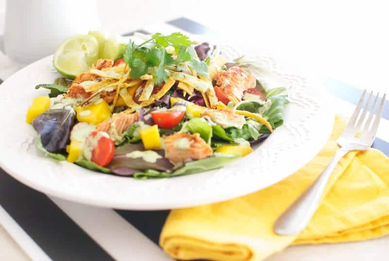 Caribbean Salad with Spicy Salmon and Creamy Tomatillo Dressing on a white plate and yellow napkin to the side