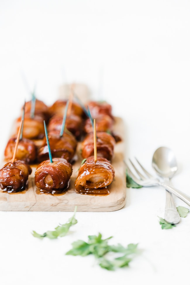 Bacon wrapped water chestnuts on a wooden cutting board.