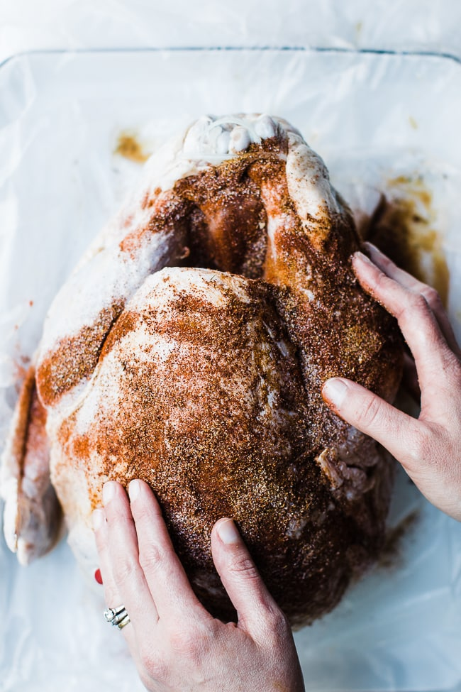gently rubbing a turkey with spices
