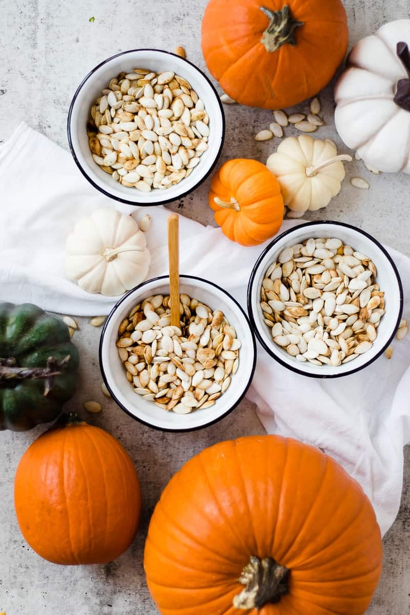 roasted pumpkin seeds in bowls with fresh pumpkins