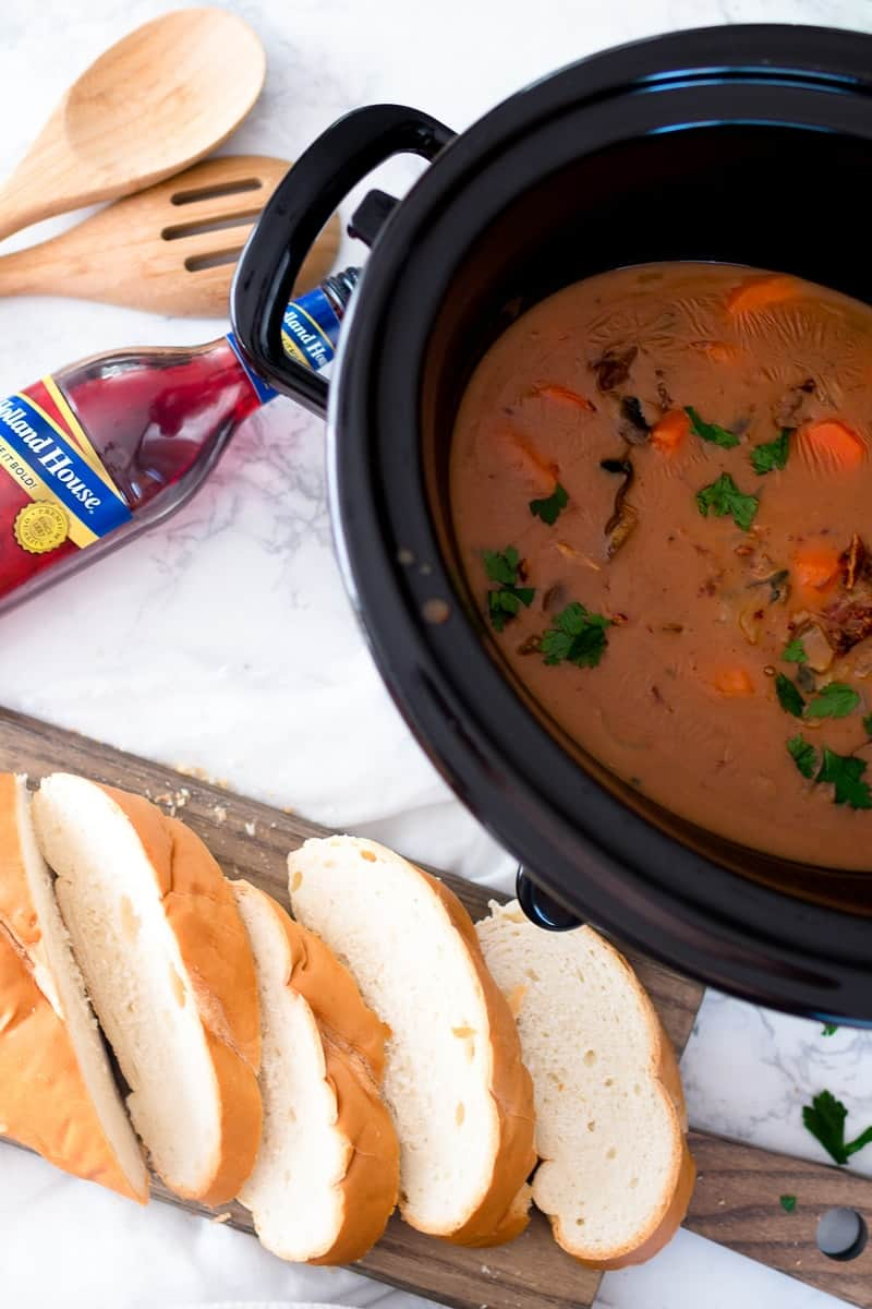 Slow Cooker with bourguignon ingredients, sliced bread on the side