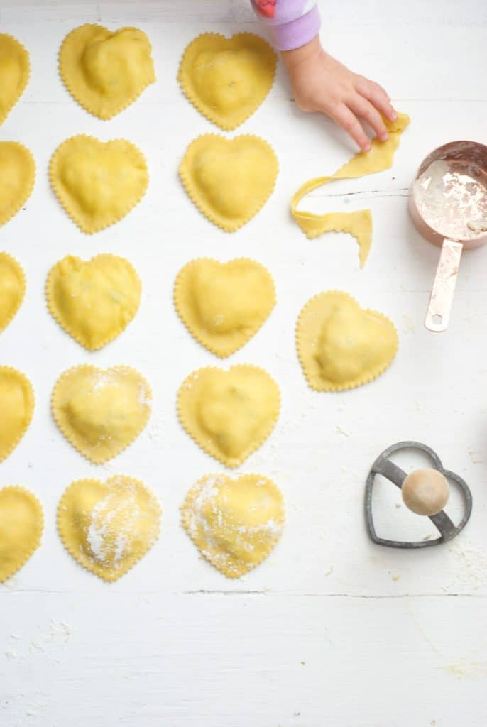 Ricotta and Basil Heart Raviolis laid out, with child's hand reaching for dough