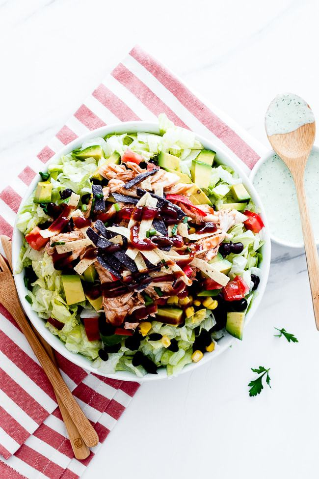 bbq chicken salad cpk in a white bowl with a red striped napkin and wooden utensils