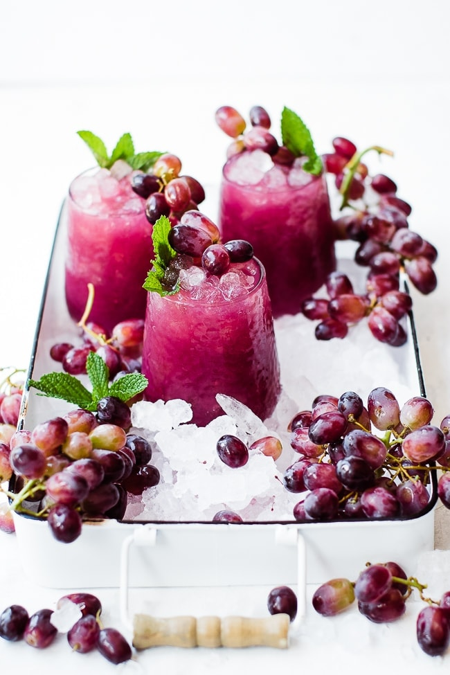 three cups of grape juice, ice, and grapes