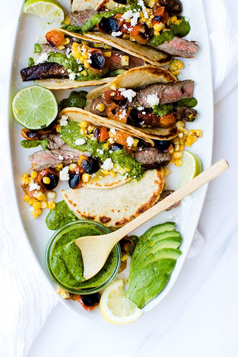 Chimichurri Steak Tacos on a serving plate with extra sauce and toppings