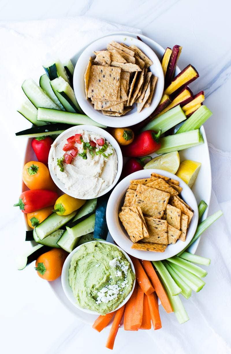 Lemon Basil Hummus on tray with crackers and dipping veggies