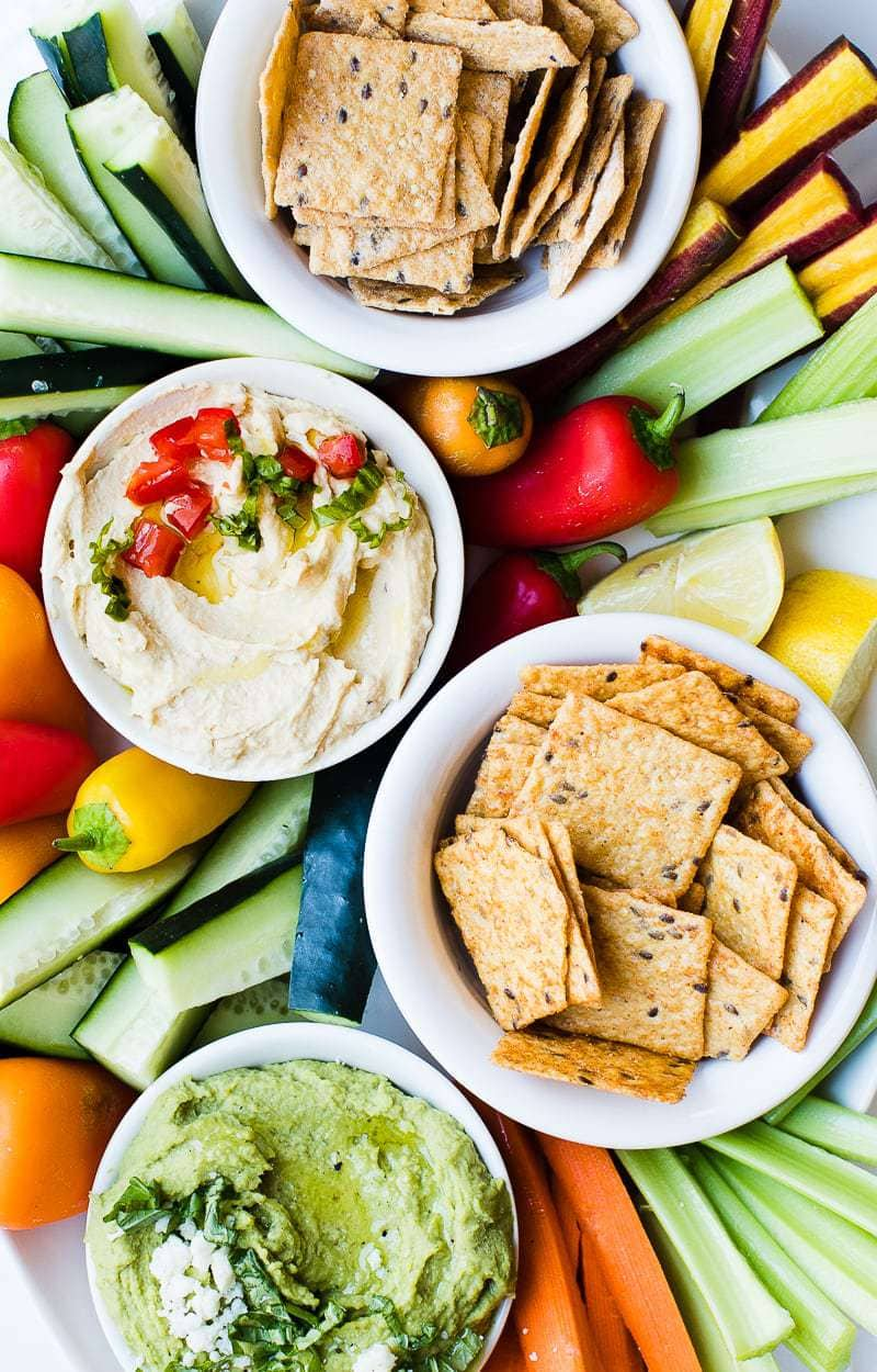 Lemon Basil Hummus in bowl with crackers and fresh vegetables surrounding it