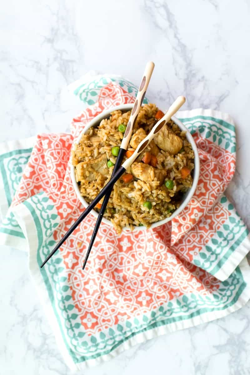 chicken-fried-rice in bowl over patterned cloth with chopsticks