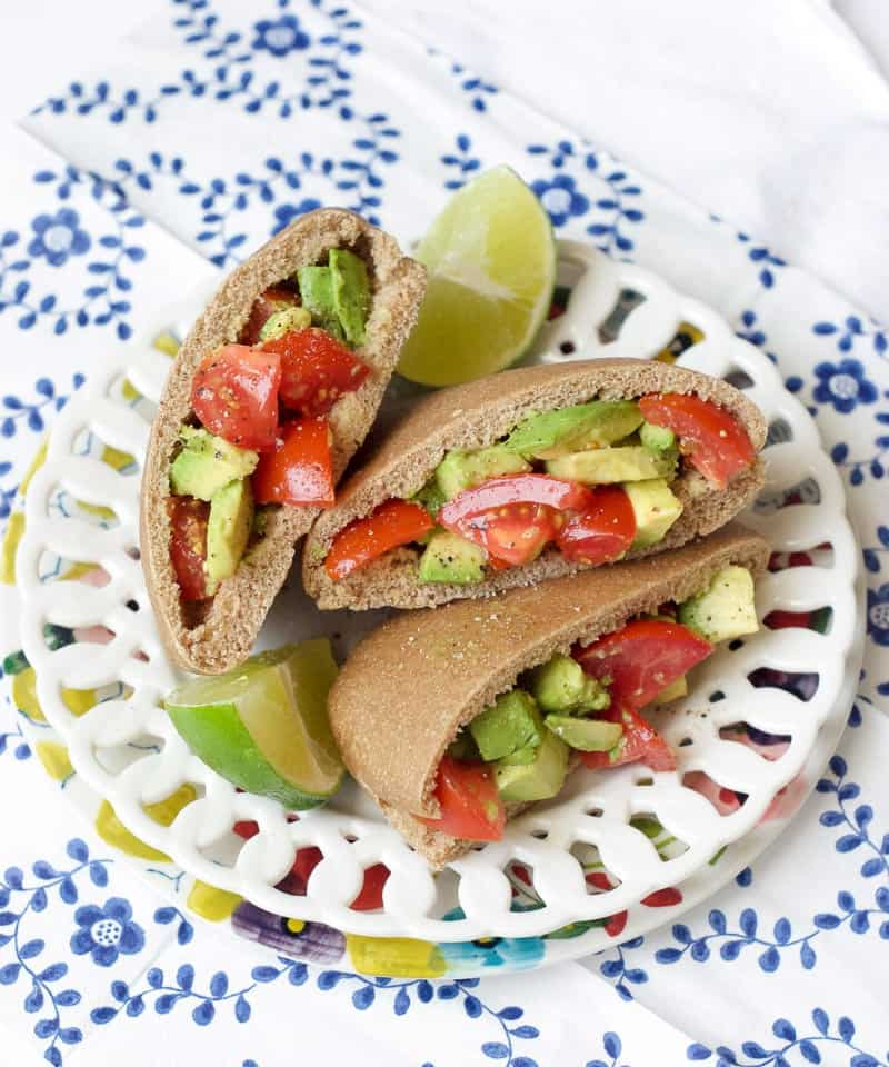 Tomato and Avocado Pitas on bowl atop patterned tablecloth