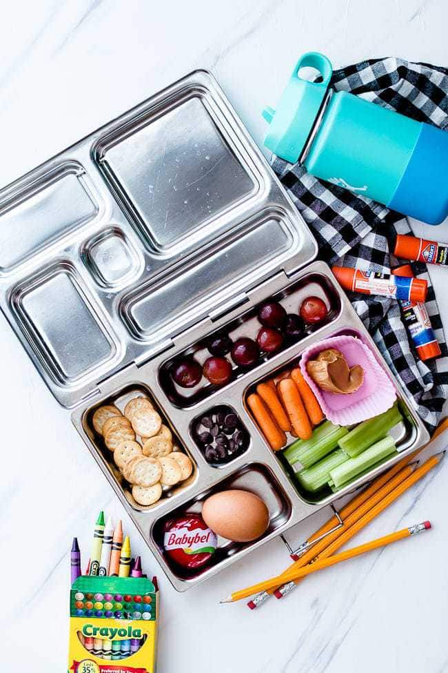 Non-sandwich school lunch with veggies, cheese, and peanut butter in a stainless steel lunchbox.