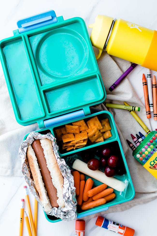 non-sandwich school lunch with a hotdog, cheese, fruit, and crackers in a turquoise lunchbox.