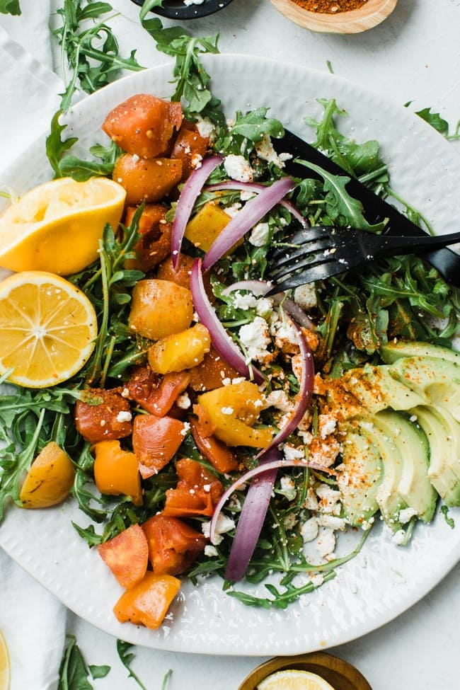 plate of salad with tomatoes lemon and avocado