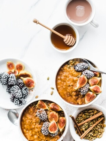 Pumpkin Pie Oatmeal in white bowls topped with blackberries and figs.