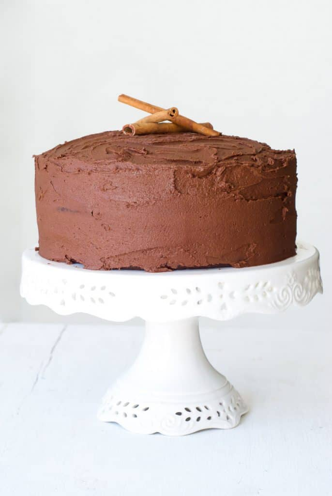 Cinnamon Chocolate Cake with frosting on a white cake stand