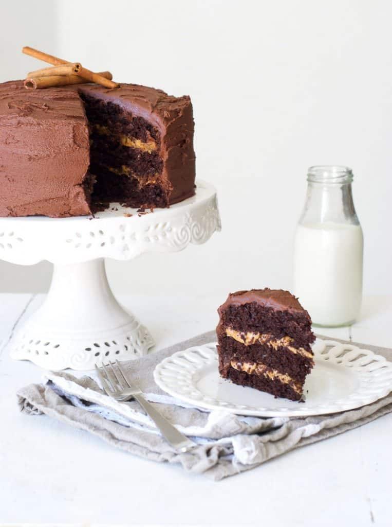 Cinnamon Chocolate Cake on a cake stand and a slice on a plate