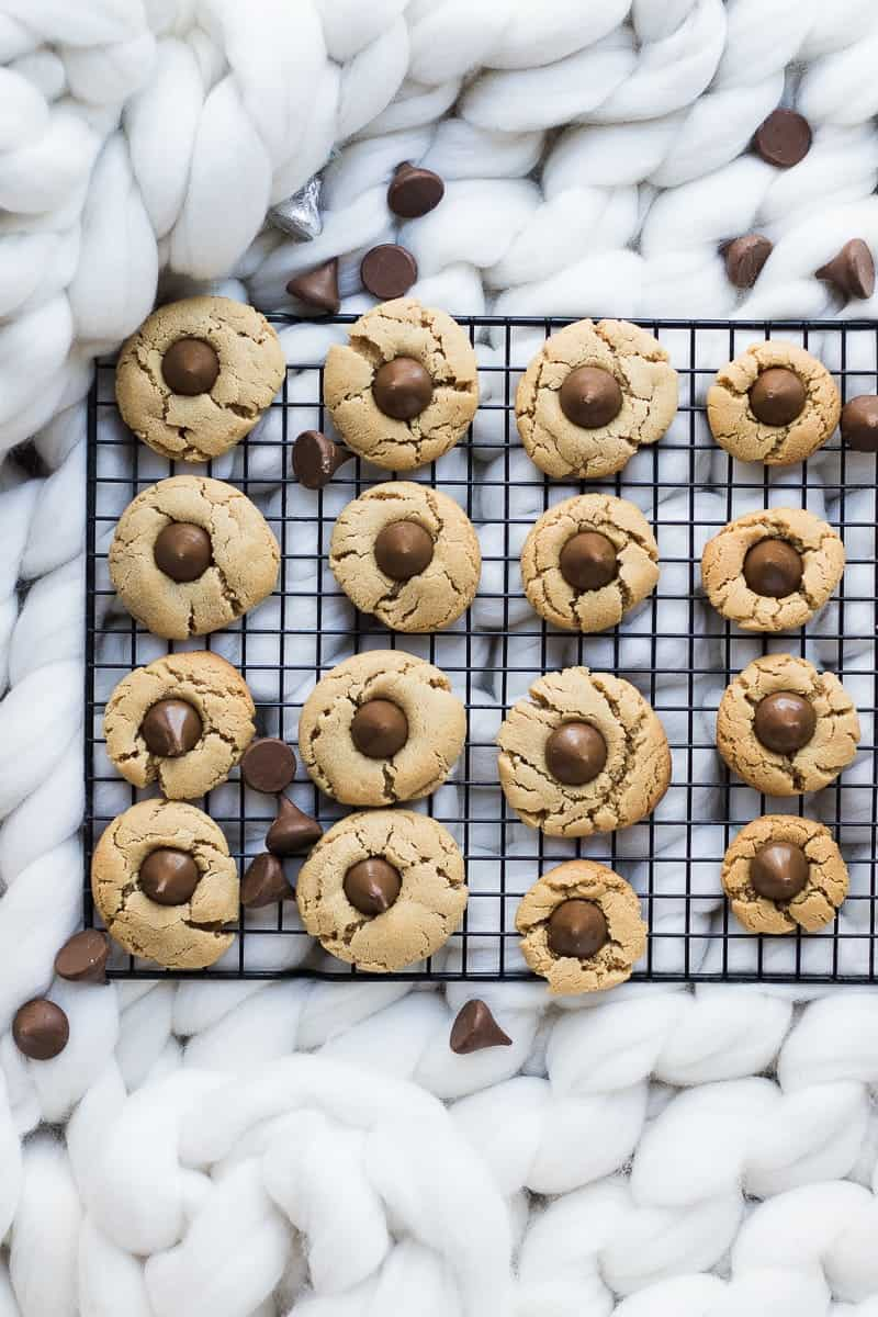 Peanut Butter Blossom cookies on a cooling rack with chocolate chips